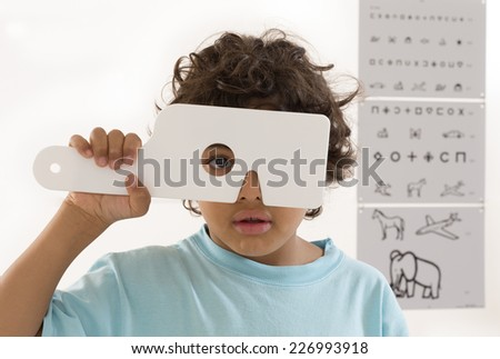 Young boy s having eye exam performed by optician, optometrist or eye doctor. - stock photo