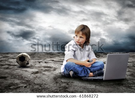 Young boy seating with notebook on the land