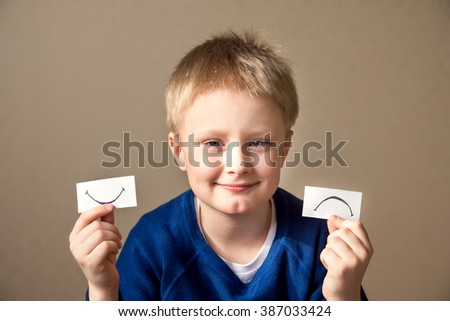 Young boy select between positive and negative expressions - stock photo
