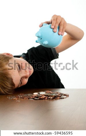 Young Boy Shaking Money out of Blue Piggy Bank - stock photo