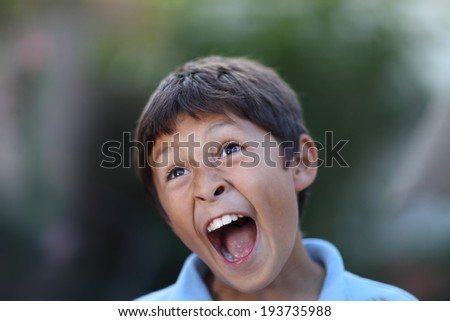 Young boy shouts loudly - having fun outside - with shallow depth of field