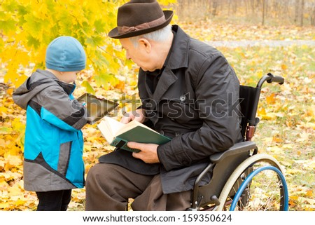 Young boy showing his grandfather something on his tablet computer as the old man sits in a wheelchair in his overcoat and hat enjoying a book in a colourful autumn garden - stock photo