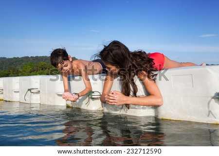 Young boy showing his sister tiny prawns he caught while they were on floating platform on tropical island - stock photo