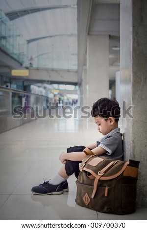 Young boy sitting alone in a  corridor of airport at feeling sad mood. - stock photo