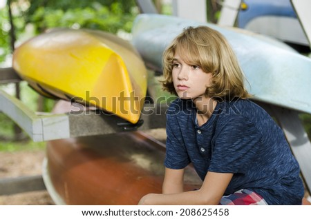 Young boy sitting and thinking after racking the kayaks - stock photo