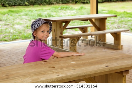 Young boy sitting at a picnic table - stock photo