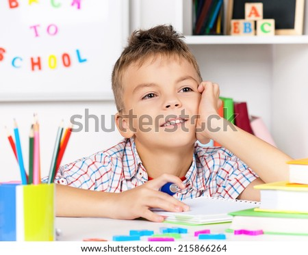 Young boy sitting at desk in the classroom, doing homework at the table