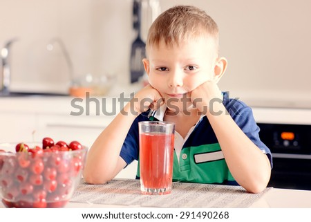 Young Boy Sitting at Kitchen Table Leaning on Elbows and Smiling at Camera with Glass of Red Juice and Bowl of Ripe Cherries