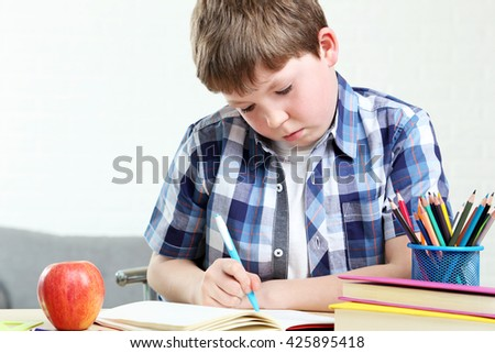 Young boy sitting at the desk and reading book - stock photo