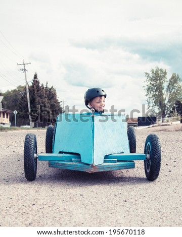 Young boy sitting in a blue homemade soap-box car - stock photo