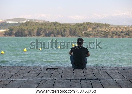 Young boy sitting in a pier - stock photo