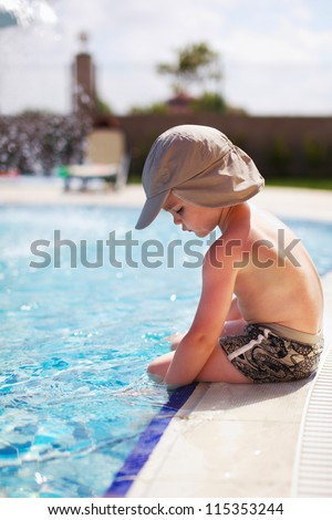 young boy sitting in a pool - stock photo
