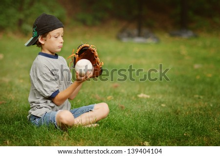 young boy sitting in the grass with his glove and ball - stock photo