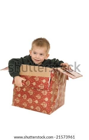 Young boy sitting inside Christmas box smiling. Isolated on white.