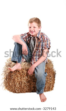 young boy sitting on a bale of hay. - stock photo