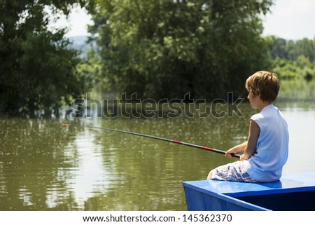 young boy sitting on a boat and fishing - stock photo