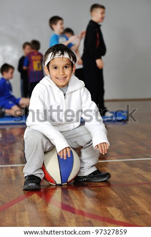 Young boy sitting on basketball, his friends in background