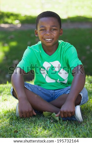 Young boy sitting on grass in recycling tshirt on a sunny day - stock photo