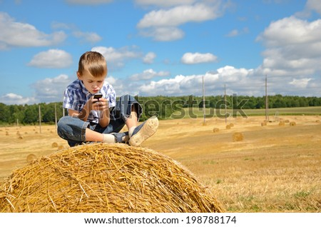young boy sitting on haystack in the field and playing with his  phone - stock photo