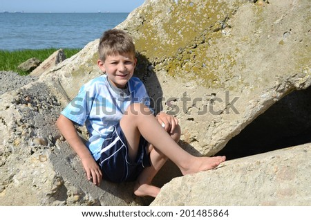 young boy sitting on rocks by the beach - stock photo