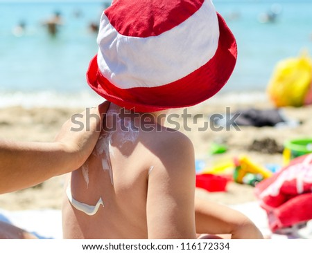 Young boy sitting on the beach during his summer vacation having sunscreen applied to his back by a parent to prevent burning from harmful UV rays - stock photo