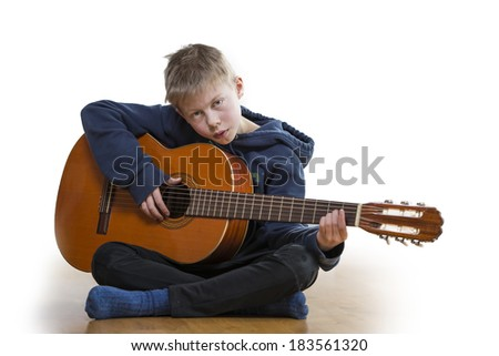 Young boy sitting on the floor and playing guitar on white background.