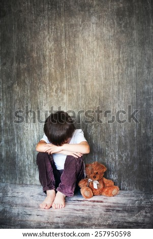 Young boy, sitting on the floor, teddy bear next to him, crying, looking away - stock photo