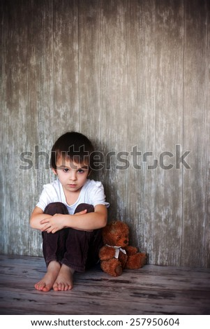 Young boy, sitting on the floor with his teddy bear, sadness in his eyes - stock photo