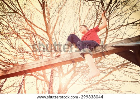 Young boy sitting on the top of a wooden swingset, toned image - stock photo