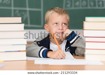 Young boy sitting working at a desk in school surrounded by two high stacks of textbooks looking up into the air with a resigned expression - stock photo