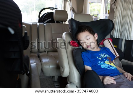 Young boy sleeping in the carseat