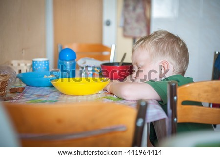 Young boy sleeping while eating at the table with plate and cup - stock photo
