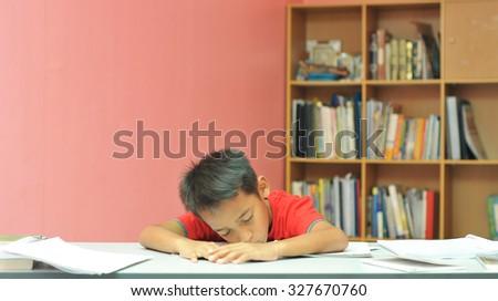 young boy sleeping while studying  - stock photo