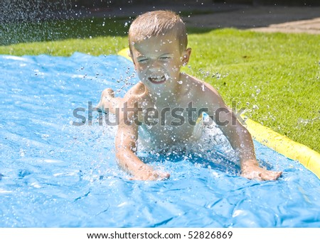 Young boy sliding on a water slide in the back yard