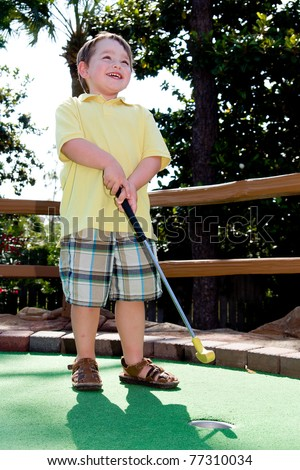 Young boy smiles while playing mini golf on putt putt course. - stock photo