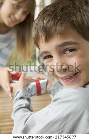 Young boy smiling and taking gift from mother