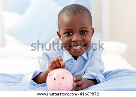 Young boy smiling at the camera while putting money into his piggy bank