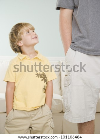 Young boy smiling up at father - stock photo