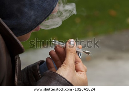 Young boy smoking marijuana with a glass pipe - stock photo
