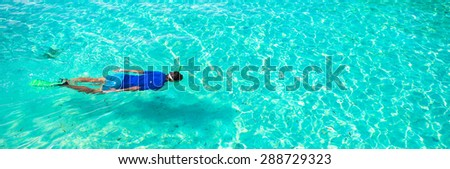 Young boy snorkeling in tropical turquoise ocean