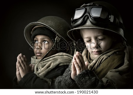 Young boy soldiers praying - stock photo