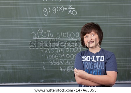 Young boy solving a maths problem in class standing with a piece of chalk in his hand in front of the blackboard covered in numbers