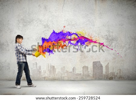 Young boy splashing colorful paint from bucket - stock photo