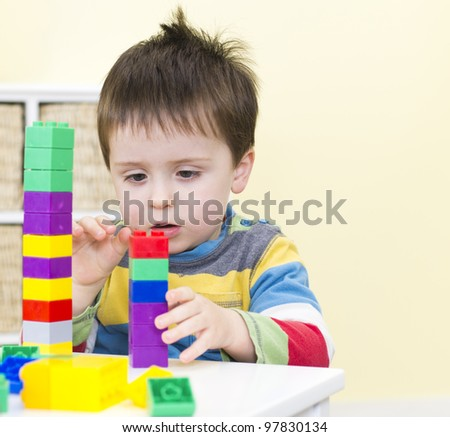 Young boy stacks connecting blocks - stock photo