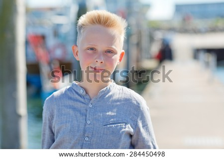 young boy standing harbor in background - stock photo