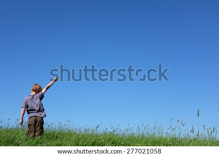 Young boy standing in meadow pointing to sky - stock photo