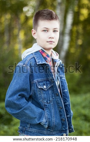 Young boy standing in the park - stock photo