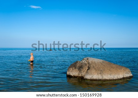 Young boy standing in the water near the beach close to a rock and enjoying the warm summer weather, island Oeland, Sweden - stock photo