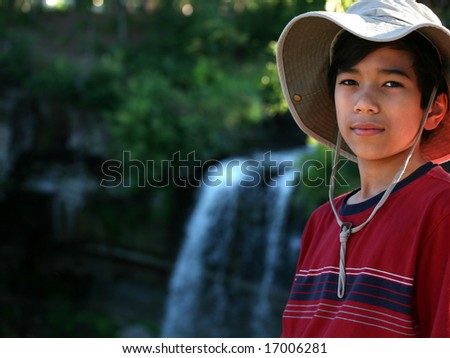 Young boy standing next to water fall