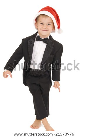 Young boy standing with tuxedo on and Santa hat. Isolated on white.